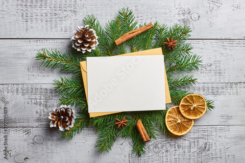 Christmas mockup with empty greeting card and fir tree branches with decorations
