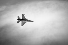 Fighting Jet F-16 Cuts The Cloudy Sky Above. Black And White, Bottom View.