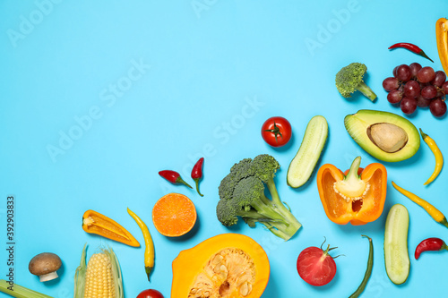 Flat lay composition with fresh organic fruits and vegetables on light blue background. Space for text