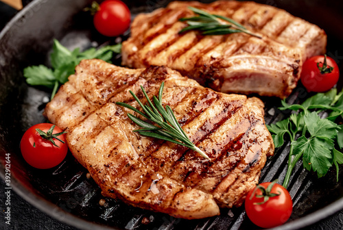 Fototapeta grilled pork steaks in a grill pan with spices   obraz