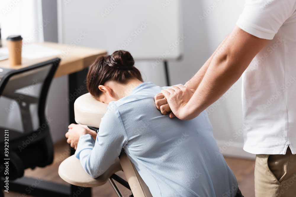 Fototapeta Massage therapist massaging brunette woman back sitting on massage chair with blurred office on background