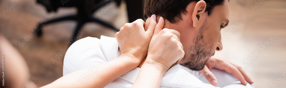 Fototapeta Female massage therapist with outstretched hands massaging neck of businessman on blurred foreground, banner