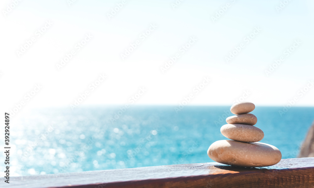 Fototapeta Zen relax background. A pyramid of stones on the beach in clear sunny weather. Background for meditation, yoga and massage