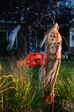 Scarecrow In Front Yard With Halloween Decorations