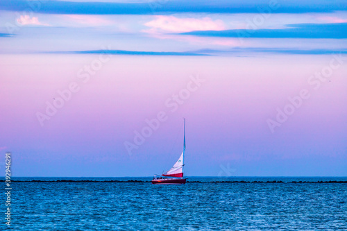 Foto White sailboat sailing in the Nantucket Harbor under a purple sky