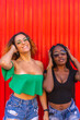 canvas print picture - Lifestyle of friends, Caucasian blonde girl and black girl with big braid on a red background. Enjoying a summer afternoon