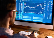 Business Man Trader Broker Looking At Pc Computer Screen, Investor Manager Analyzing Financial Chart, Exchange Trading Online Investment Data Crypto Currency Stock Market Graph, Over Shoulder View.