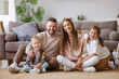 canvas print picture happy family mother father and children at home on floor next to sofa.