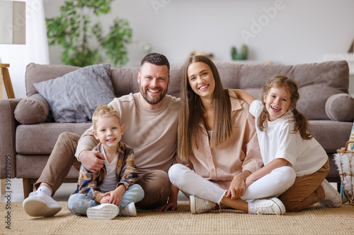 Canvastavla happy family mother father and children at home on floor next to sofa