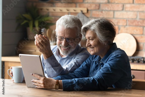 Fototapeta Happy mature couple having fun with tablet, sitting in kitchen, laughing senior man wearing glasses drinking tea or coffee in morning, grandparents chatting with relatives online, browsing apps obraz