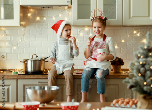 Fototapeta happy children on Christmas eve,   girl and boy eat cookies that they baked together in cozy kitchen at home