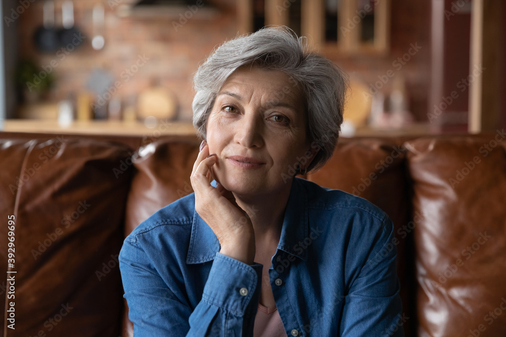 Fototapeta Head shot portrait mature woman sitting on couch at home alone, attractive focused senior middle aged grey haired female looking at camera, posing for photo, relaxing on cozy sofa indoor