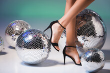Female Legs In Black Shoes And Shiny Disco Balls