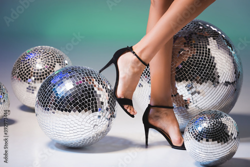 Stampa su Tela female legs in black shoes and shiny disco balls
