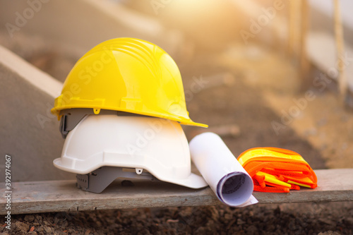 Leinwand Poster Hard hat on wooden board and blueprint building construction estate pr