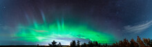 Beautiful Aurora Borealis Panorama Photo Across The Whole Horizont, Above Pine Tree Forest And City Lights In Swedish Countryside Close To Umea City, Vasterbotten County. Ume River Delta Area.