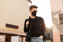 Young Handsome Stylish Man Model In Stylish Black Denim Jacket With Backpack In Vintage Sunglasses In Black Trendy Protective Mask Poses In City On Bright Spring Sunny Day. Cool Guy Hipster In Street.