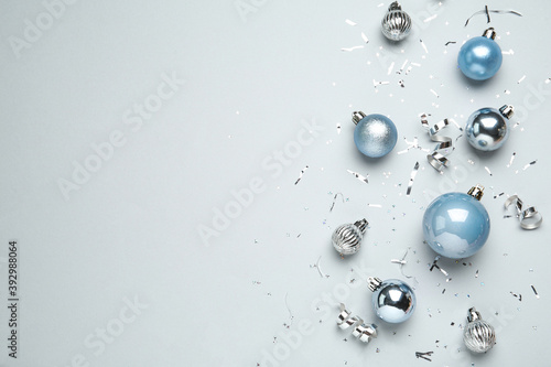 Flat lay composition with shiny Christmas balls, confetti and streamers on light background, space for text