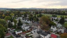 Old Small Town In America. Houses Along Street As Car Passes By Under Sunset, Sunrise Sky. Aerial Establishing Shot.