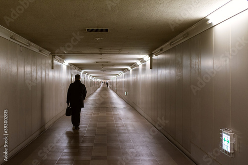 Silhouette of man walking in dark and long underground passage 暗く長い地下道を歩く男性のシルエッ Fotobehang