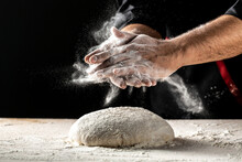 Hand Clap Of Professional Chef With Bowl For Cooking And Baking Utensils With Splash Flour On Dark Background. Isolated On Dark Background. Empty Space For Text