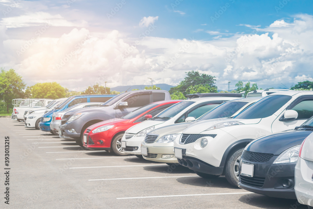 Fototapeta Car parked in large asphalt parking lot with beautiful cloud and blue sky background. Outdoor parking lot  travel transportation technology with nature