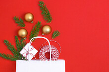 Paper Bag On Red Background. With Gift Box, Balls, Christmas Tree Christmas Gift Preparation Concept.