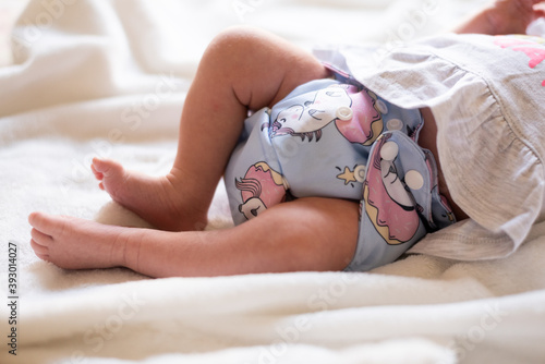 Vászonkép A baby lying on a bed with a white blanket where the focus is on her legs and non disposable diaper