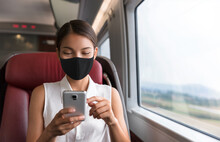 Asian Business Woman Using Mobile Phone During Commute To Work In Public Transport Train Wearing Face Mask For Corona Virus Prevention.