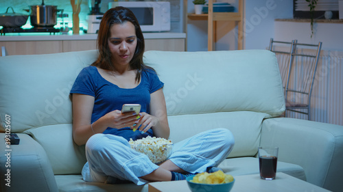 Woman scrolling on phone eating popcorn and watching a movie Canvas Print