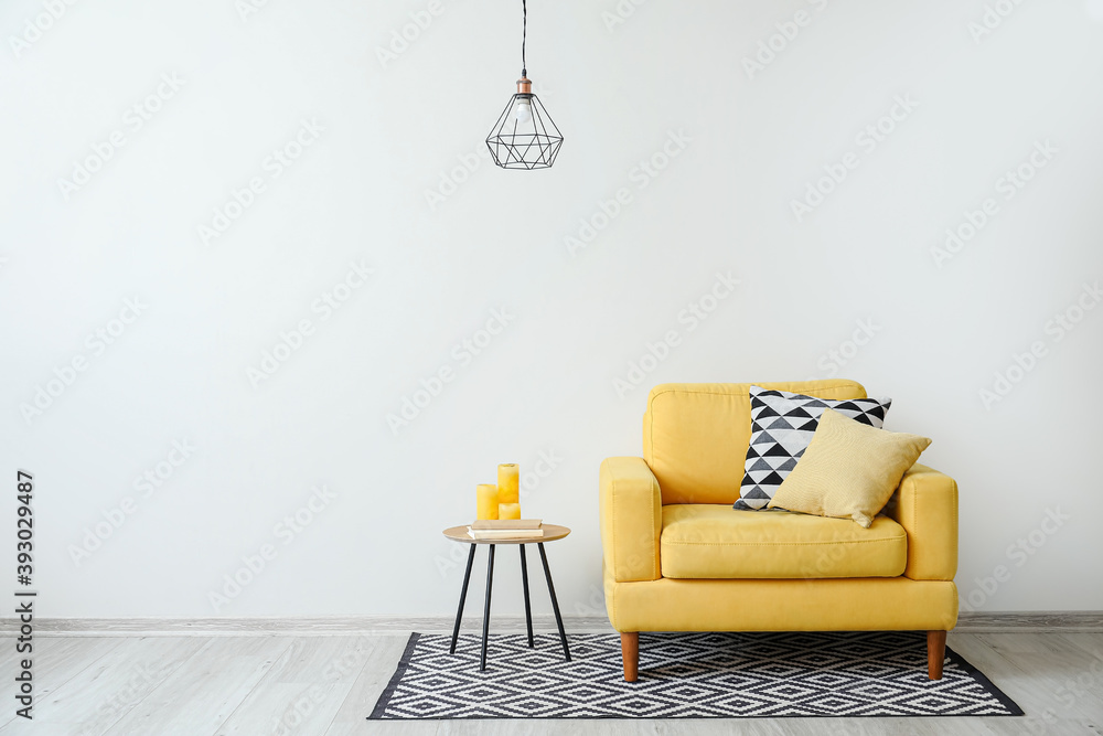Fototapeta Stylish armchair with pillows and table with candles near light wall in room