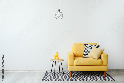 Fototapeta Stylish armchair with pillows and table with candles near light wall in room obraz