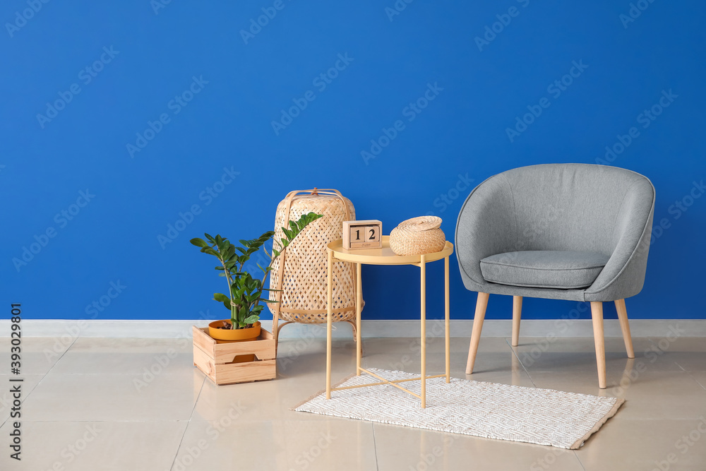 Fototapeta Stylish armchair with table and lantern near color wall in room