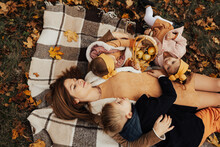Beautiful Mother, Two Little Daughters And Son Hugging On An Autumn Picnic In Park While Lying On The Plaid.