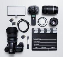 Videography And Photography Equipment - Top View Flat Lay Of Modern Dslr Camera, Lenses, Filters, Microphone With Windscreen, Led Light, Memory Cards And Clapper Board Over White Table
