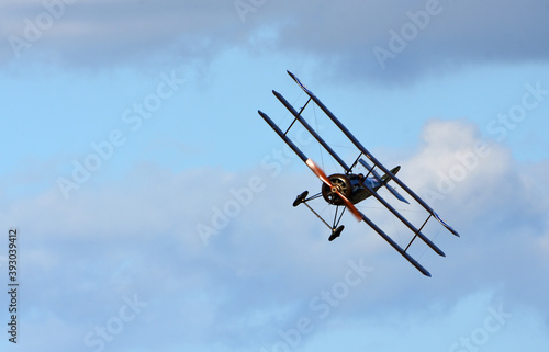 Fototapeta Vintage  Sopwith Triplane  in flight blue sky  and clouds view from front