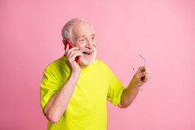 Photo Of Old Cheerful Positive Man Hold Glasses Wear Lime T-shirt Talk Speak Phone Isolated On Pink Color Background