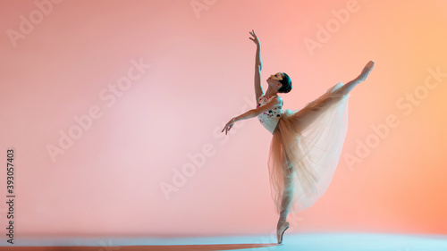 Young slim ballerina in light long dress is dancing on colored background with b Wallpaper Mural