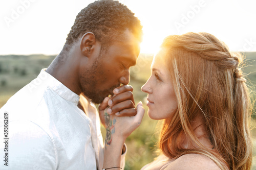 Touching portrait of multiracial couple in sunset light Fotobehang