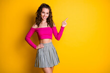 Photo Portrait Of Schoolgirl Pointing Finger At Blank Space Hand On Waist Wearing Fuchsia Top Checkered Mini Skirt Isolated On Bright Yellow Colored Background