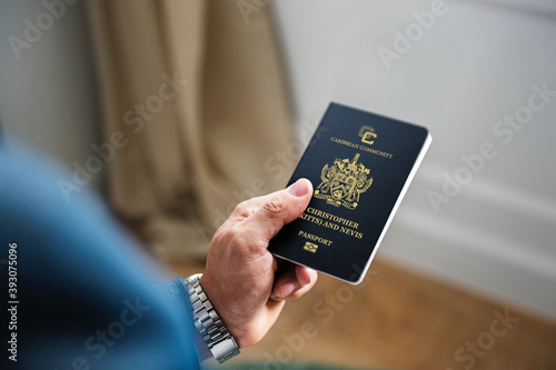 A hand holds a Saint Kitts and Nevis passport, focusing the lens on it Fototapet