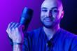 Leinwandbild Motiv Black man with camera standing against purple background in neon light