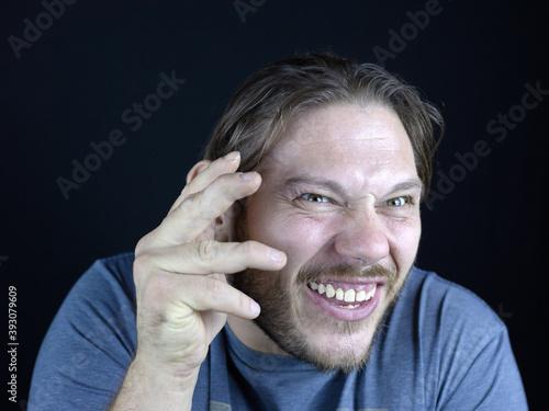 Obraz na plátně Close-up shot of a male making a goofy face