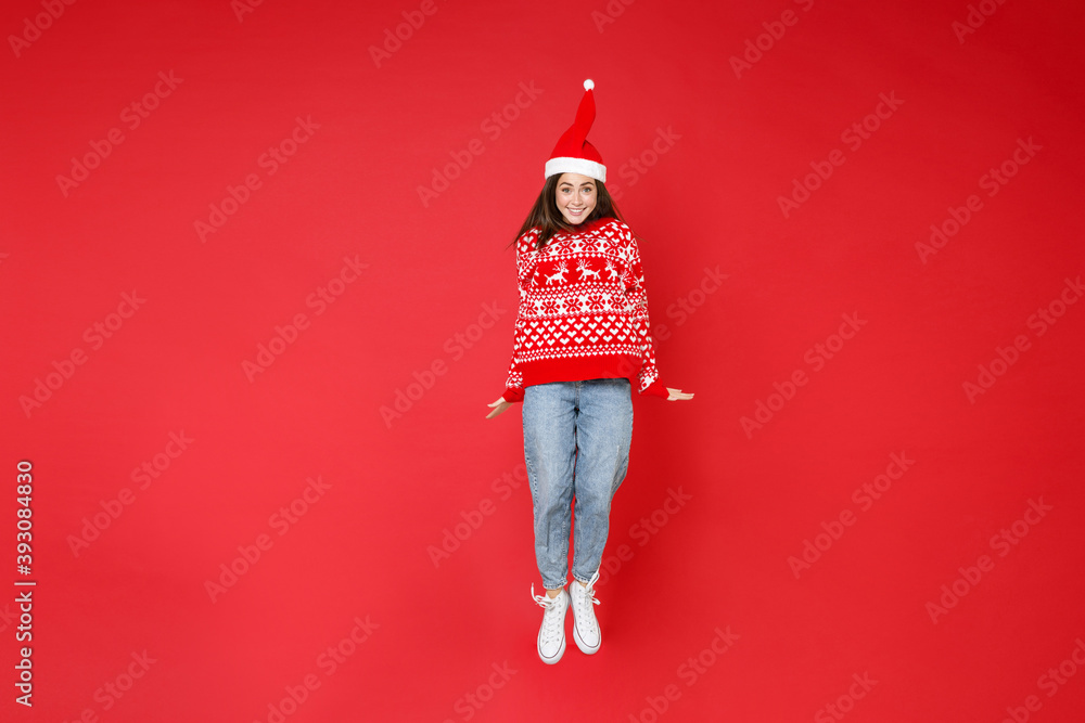 Fototapeta Full length of smiling young brunette Santa woman 20s wearing sweater, Christmas hat jumping having fun isolated on red background, studio portrait. Happy New Year celebration merry holiday concept.