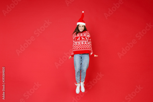 Obraz Full length of smiling young brunette Santa woman 20s wearing sweater, Christmas hat jumping having fun isolated on red background, studio portrait. Happy New Year celebration merry holiday concept. - fototapety do salonu