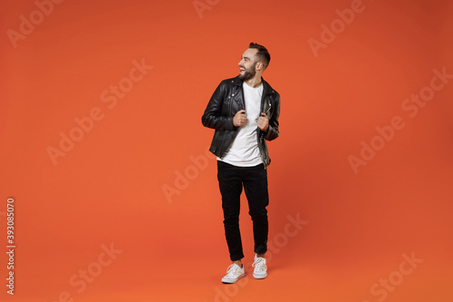 Obraz Full length of cheerful laughing funny excited young bearded man wearing basic white t-shirt black leather jacket standing looking aside isolated on bright orange colour background studio portrait. - fototapety do salonu
