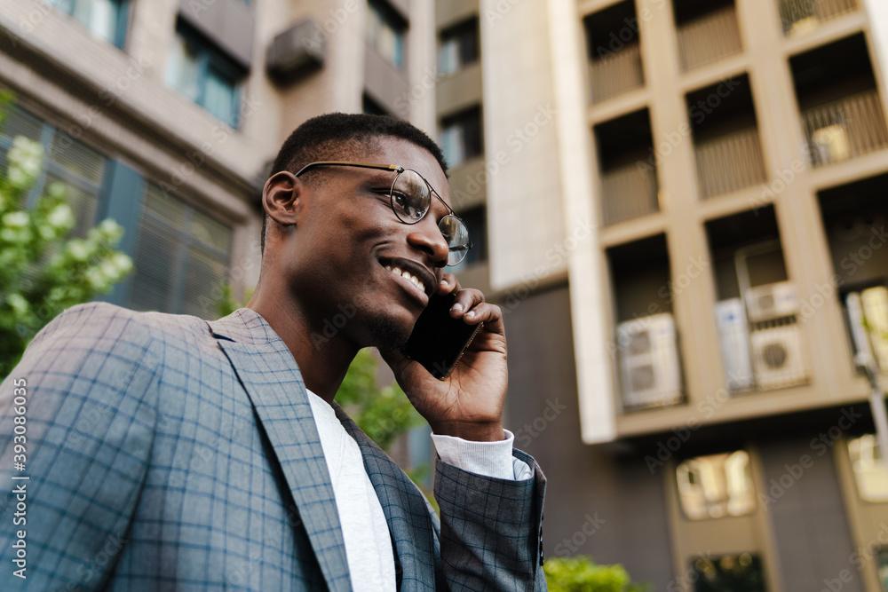 Fototapeta Joyful african american man talking on mobile phone while walking on street