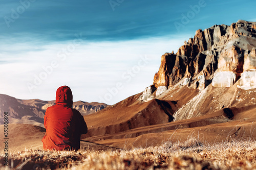 Obraz Woman in red jacket sitting alone in the mountains in Russia North Caucasus enjoying landscape. Travel lifestyle vacations tourism outdoor trip Back view - fototapety do salonu
