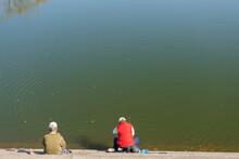 秋の公園の池で釣りをしている人