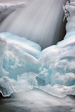 Winter Landscape Of A Cascade Captured With Motion Blur And Framed By Blue Ice, Gull Creek, Michigan, USA